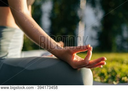Close-up View Of Hands Of Young Woman Holding Fingers On Knee In Yoga Mudra Position While Sitting A