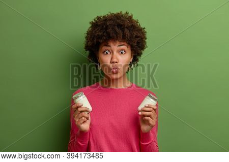 Lovely Affectionate Woman Keeps Lips Rounded, Holds Two Bottles Of Yoghurt, Eats Healthy Food, Has P