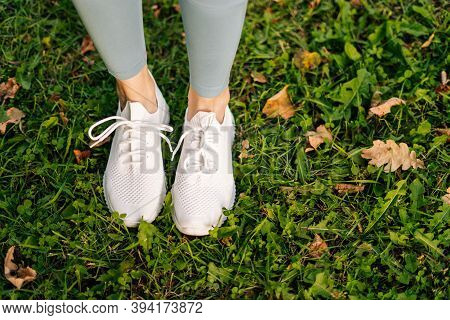 Close-up Top View Of Unrecognizable Woman Feet In White Sneakers Standing And Poses In Place On Gree