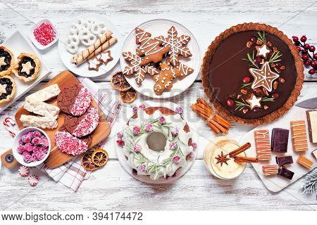 Variety Of Christmas Holiday Desserts And Sweets. Above View Table Scene Over A White Wood Backgroun