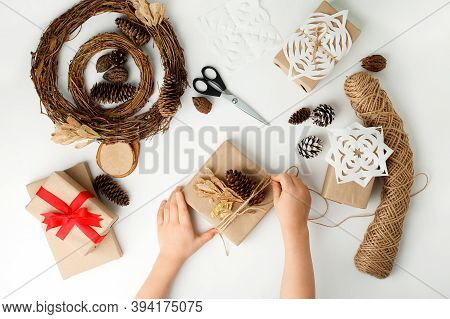 Child's Hands Making Christmas Gift. Flat Lay, Top View, Kid Hands Wrapped Gift Box In Craft Paper,