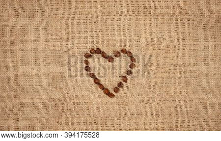 Heart symbol made by coffee beans heart-shaped pattern on rustic burlap fabric background.