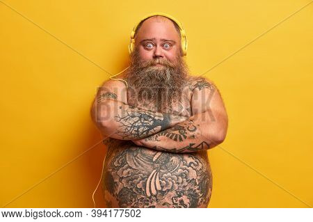 Chubby Male Meloman Stands With Arms Folded, Looks Confident At Camera, Has Tattooed Body, Listens M