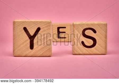 Yes Word On Wooden Cubes. Yes Message Made With Building Blocks. Copy Spaceyes Lettering On Pink Bac