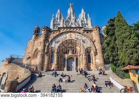 BARCELONA, SPAIN - NOV 07 -2020: People relaxing in front of Tibidabo church on mountain in Barcelona