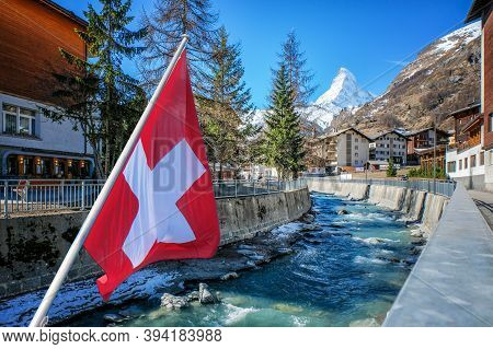 Beautiful View Of Zermatt Village And Matterhorn, With Swiss Flag, Switzerland.
