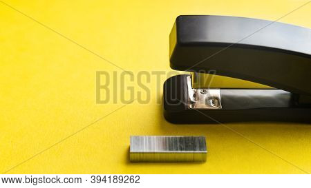 A Set Of Office Supplies Stapler And Staples On Yellow Background.