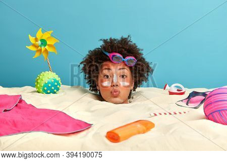 Outdoor Shot Of Young Curly Woman In Romantic Mood, Spends Time At Beach, Applies Sunscreen Cream To