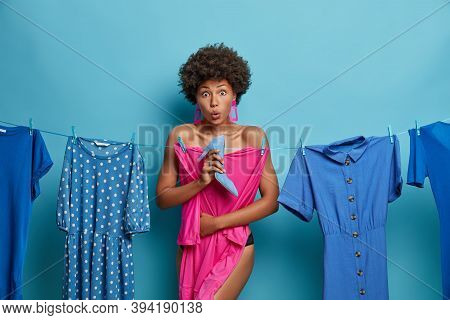 Indoor Shot Of Surprised Young Woman Chooses Clothes For Desired Event, Poses Near Dresses Hanging O