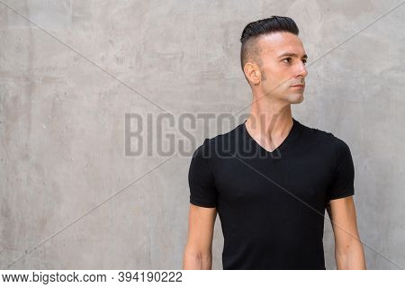 Portrait Of Handsome Young Italian Man With Undercut Wearing Black T-shirt And Thinking