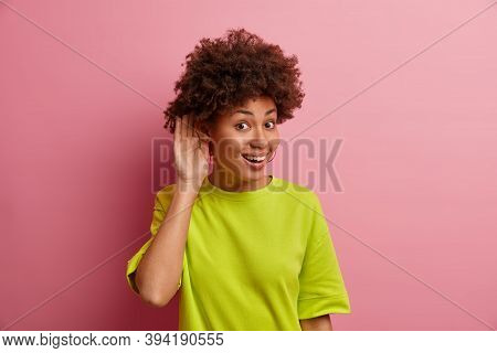 What You Say. Positive Ethnic Woman Keeps Hand Near Ear To Hear Gosipping Better, Eavesdropes Privat