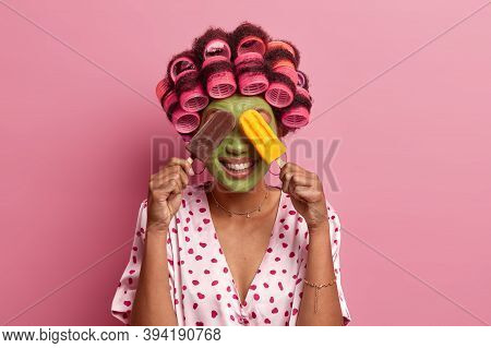 Positive Woman Covers Eyes With Two Delicious Ice Creams, Smiles Happily, Applies Green Facial Mask