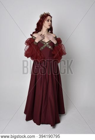 full length portrait of pretty woman wearing red medieval gown with gold crown. Standing pose, again
