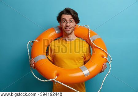 Pleased Cheerful Man Swimmer Stands With Lifebuoy, Listens Instructions From Lifesaver Before Swimmi