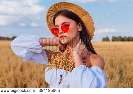 Fashion Portrait Of A Young Beautiful Woman With Straw Hat And Pink Sunglasses At Golden Oat Field W