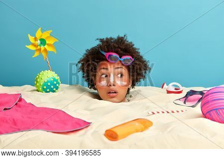 Sunbathing, Vacation And Recreation Concept. Surprised Curly Haired Young Woman Sunbathes By Sea, Lo