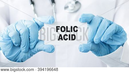 Doctor's Hands In Blue Gloves Shows The Word Folic Acid. Medical Concept.