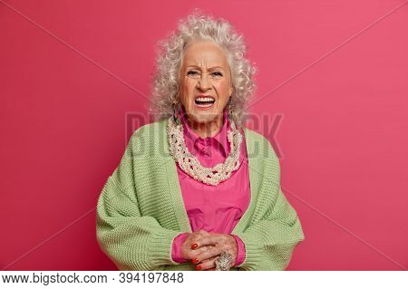 Disappointed Indignant Grey Haired Senior Woman Looks Puzzled, Smirks Face, Has White Perfect Teeth,