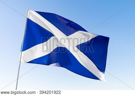Flag Of Scotland Waving Against Blue Sky