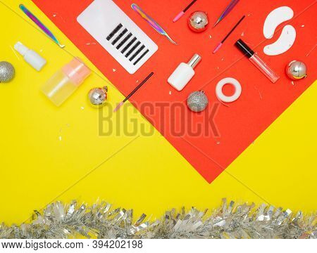 Tools For Eyelash Extension On A Red And Yellow Background. Tweezers, Artificial Eyelashes, Patches,