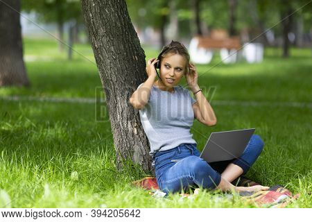 Photo Of A Smiling Student-girl During Online Lesson In Campus Parkland. She Sitting On A Grass In C