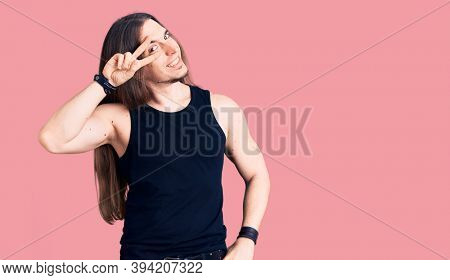 Young adult man with long hair wearing goth style with black clothes doing peace symbol with fingers over face, smiling cheerful showing victory
