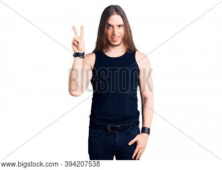 Young adult man with long hair wearing goth style with black clothes showing and pointing up with fingers number two while smiling confident and happy.