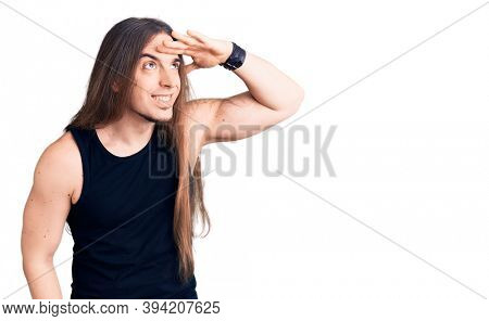 Young adult man with long hair wearing goth style with black clothes very happy and smiling looking far away with hand over head. searching concept.