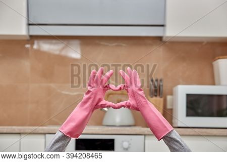 Hands In Latex Gloves Are Folded In The Shape Of A Heart In A Modern Kitchen.