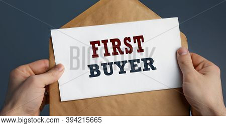 Male Hands Holding Craft Envelope With Text First Buyer On Blue Background, Communication Concept
