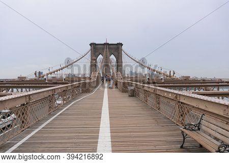 New York City, Usa - August 6, 2019:people Walk Across The Famous Brooklyn Bridge During A Cloudy Da