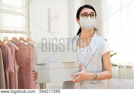 Employee in the new normal wearing mask carrying shoe boxes