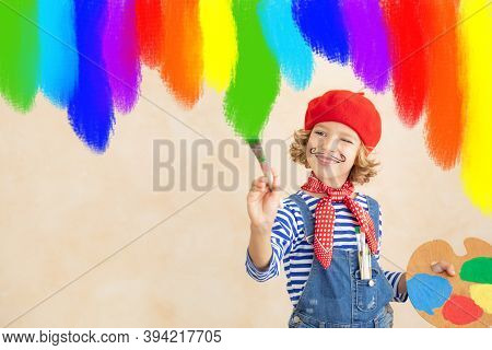 Happy Child Painting Rainbow At Home. Imagination And Childhood Dream Concept