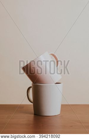 Earth tone color ceramic coffee cups on wooden table