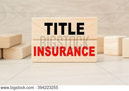 The Word Title Insurance Is Written On A Wooden Cubes Structure. Cube On A Bright Background. Can Be