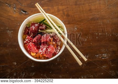 Healthy Organic Raw Tuna Poke Bowl For Takeout With Cucumber, Rice, Carrots, Onion Served In Bowl On