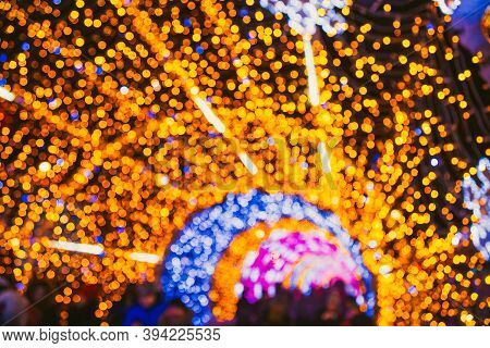 Abstract Background With Christmas Lights And Bokeh. Colored Lights Tunnel. Street Decorated For New