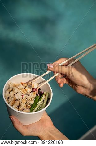 Close Up Of A Hand With Chopsticks And Healthy Organic Chicken Poke Bowl With Cucumber, Rice, Carrot