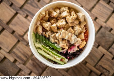 Healthy Organic Chicken Poke Bowl With Cucumber, Rice, Carrots, Onion Served In Takeout Bowl On Wood