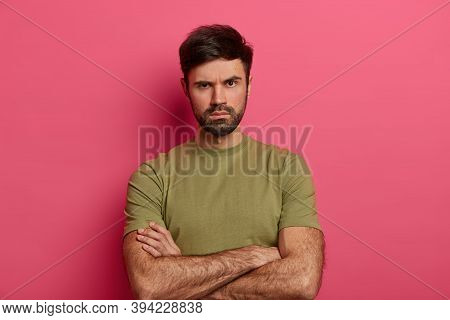 Discontent Unshaven Young Man Frowns Face, Looks With Serious Strict Expression, Keeps Hands Crossed