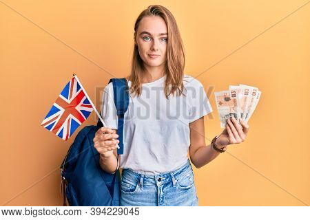 Beautiful blonde woman exchange student holding uk flag and pounds relaxed with serious expression on face. simple and natural looking at the camera.