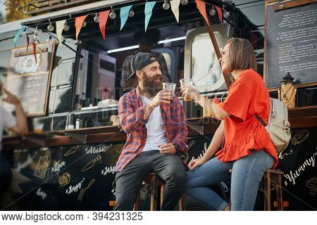 young caucasian couple toasting in front of modified truck for fast food service