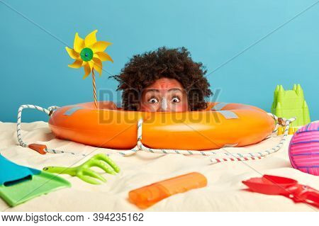 Curly Haired Woman Shocked By Her Sunburn, Has Head Stuck From Sand, Poses On Coastline Near Lifebuo