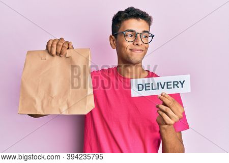Young handsome african american man holding take away paper bag with delivery text smiling looking to the side and staring away thinking.