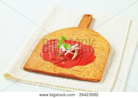 sliced meat with pepper and onion on the wooden cutting board