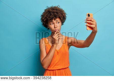 Upset Dissatisfied Young Woman With Curly Hair Looks Sadly At Smartphone Camera Makes Selfie And Wea