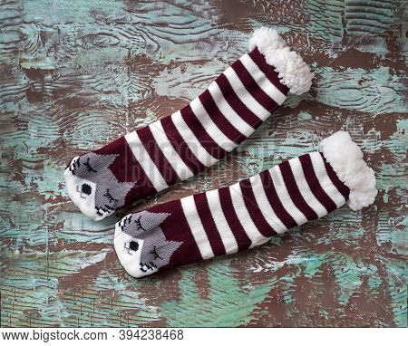 Winter Warm Striped Socks With Fur And A Cat Face On A Motley Wooden Background