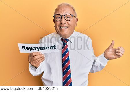 Senior caucasian man holding repayment word paper screaming proud, celebrating victory and success very excited with raised arm