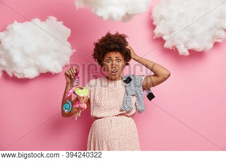 Portrait Of Funny Expectant Woman With Pregnant Belly, Poses With Clothes And Toys For Baby, Wears D