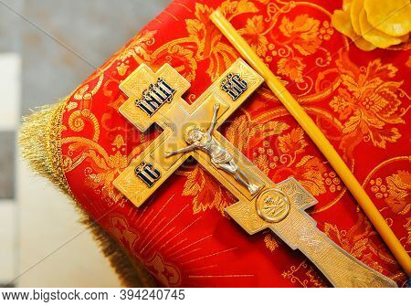 Gold Metal Orthodox Cross And Candle On Red Cloth. Details In The Orthodox Christian Church